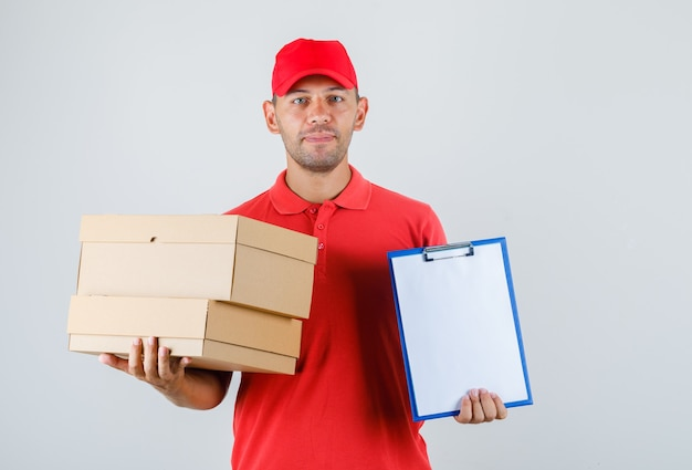 Delivery man holding cardboard boxes and clipboard in red uniform front view.