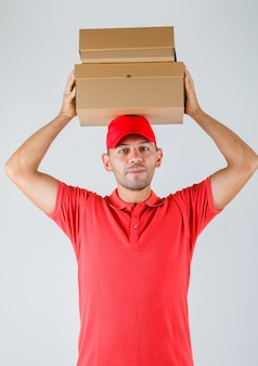 Delivery man holding cardboard boxes above his head in red uniform front view.