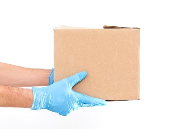 의료용 고무 장갑과 마스크에 판지 상자를 들고 있는 배달원. 복사 공간입니다. 빠르고 무료 배달 운송 . 온라인 쇼핑 및 특급 배송 . 격리