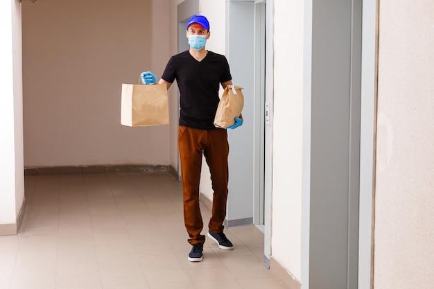 의료 고무 장갑에 판지 상자를 들고 배달 남자. 격리. 코로나 바이러스. 문 배달