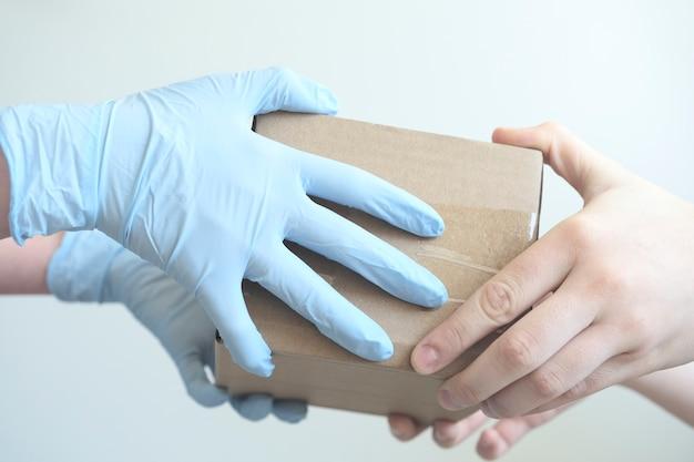 Экспедитор, держащий картонные коробки в медицинских резиновых перчатках.
