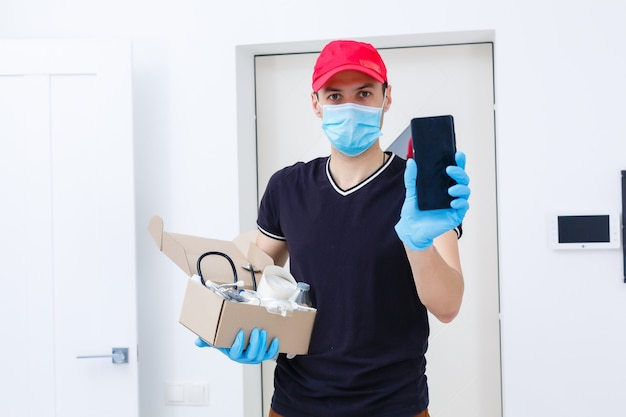 Экспедитор, держащий картонные коробки в резиновых перчатках и медицинской маске. копировать пространство. быстрая и бесплатная доставка транспортным средством. интернет-магазины и экспресс-доставка