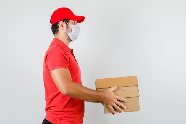 Uomo di consegna che tiene le scatole di cartone in maglietta rossa