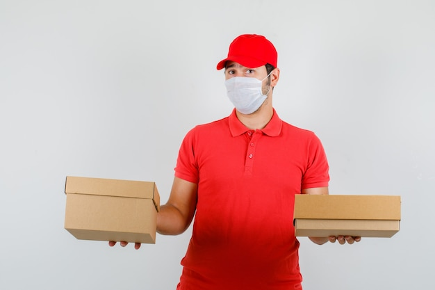 Delivery man holding cardboard boxes in red t-shirt