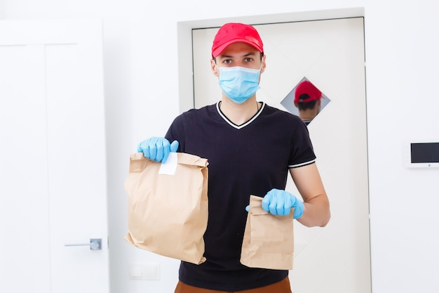 Delivery man holding cardboard boxes in rubber gloves and medical mask. copy space. fast and free delivery transport . online shopping and express delivery