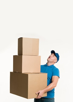 Delivery man holding cardboard boxes with copy space