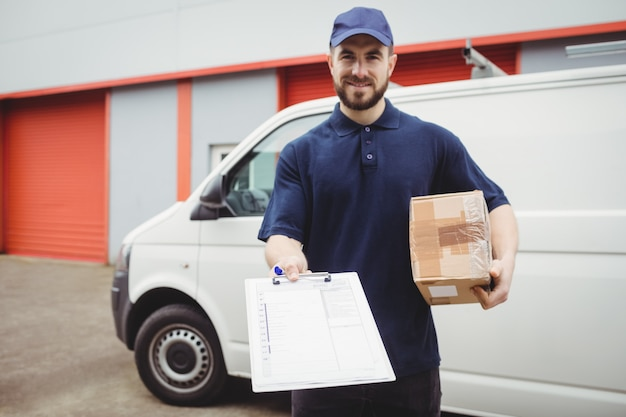 Delivery man holding clipboard and package in front of his van