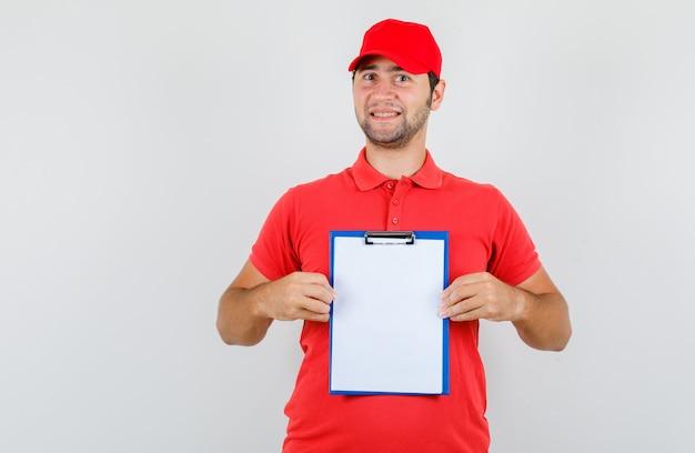 Uomo di consegna che tiene appunti in maglietta rossa