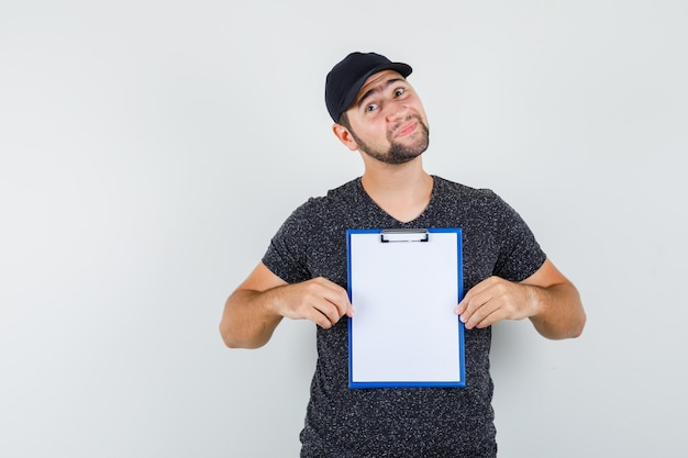 Delivery man holding clipboard in t-shirt and cap and looking positive