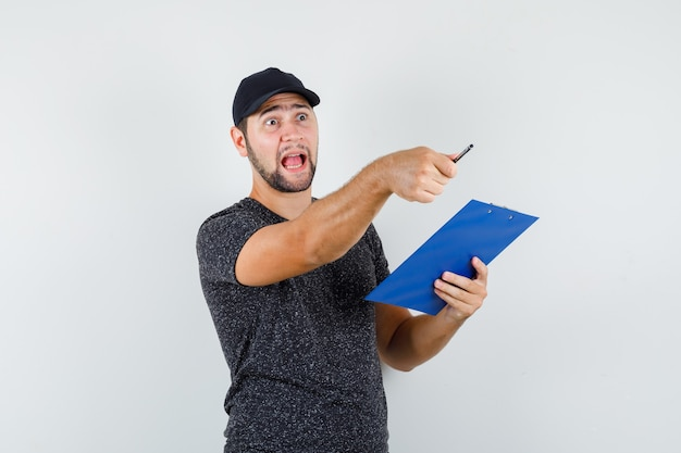 Delivery man holding clipboard while pointing away in t-shirt and cap and looking angry