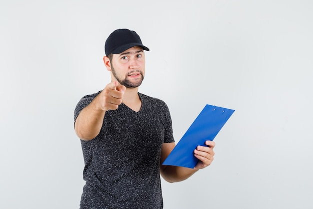 Delivery man holding clipboard while pointing at camera in t-shirt and cap front view.
