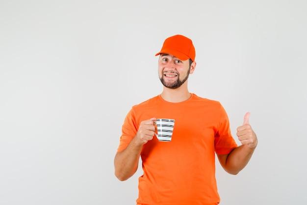 Fattorino che tiene tazza di bevanda con il pollice in su in maglietta arancione, berretto e guardando allegro, vista frontale.
