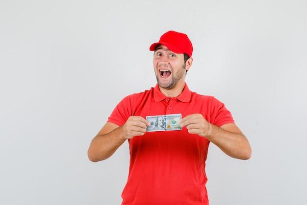 赤いtシャツでドル紙幣を保持している配達人