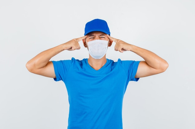 Uomo di consegna che tiene le dita sulle tempie in maglietta blu