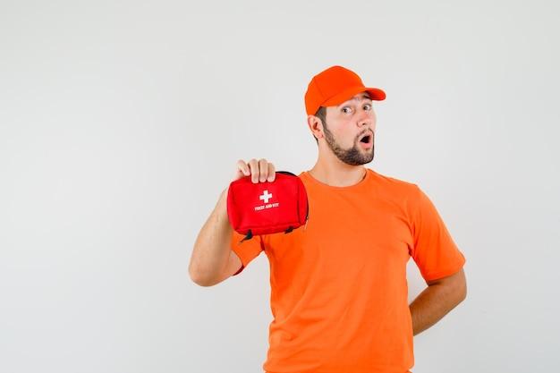주황색 티셔츠, 모자를 쓰고 놀란 표정으로 구급 상자를 들고 있는 배달원. 전면보기.