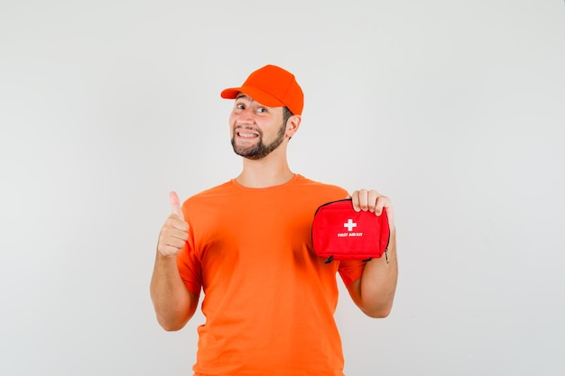 주황색 티셔츠, 모자를 쓰고 쾌활해 보이는 구급 상자를 들고 있는 배달원. 전면보기.