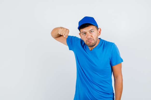 Delivery man holding fist for threatening in blue t-shirt