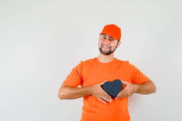 오렌지 티셔츠, 모자, 그리고 쾌활한 찾고 선물 상자를 들고 배달 남자. 전면보기.