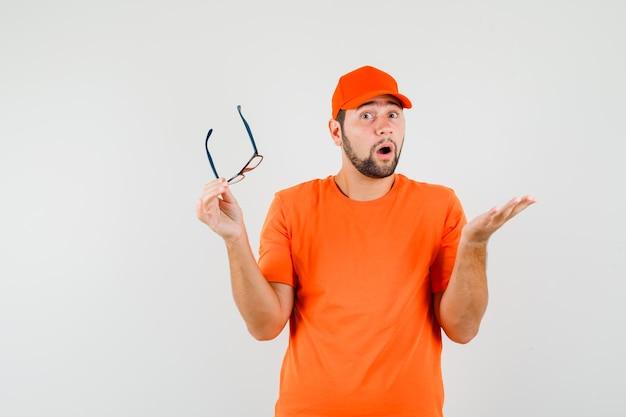 오렌지 티셔츠, 모자를 쓴 안경을 들고 어리둥절해 보이는 배달원. 전면보기.