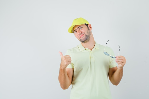 Delivery man holding glasses, showing thumb up in yellow uniform and looking confident. front view.