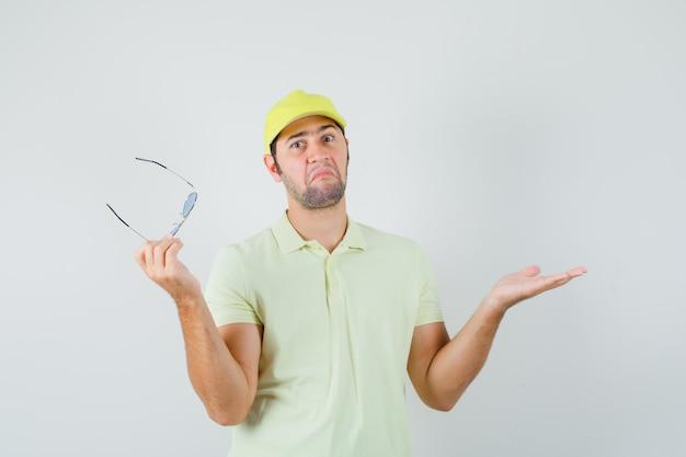 Uomo di consegna che tiene i vetri in uniforme gialla e che sembra confuso. vista frontale.