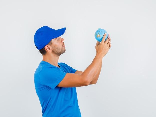 Uomo di consegna che tiene globo in maglietta blu