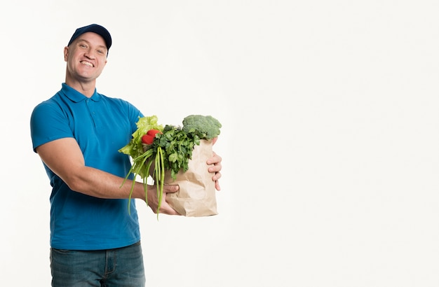 Delivery man holding grocery bag with copy space