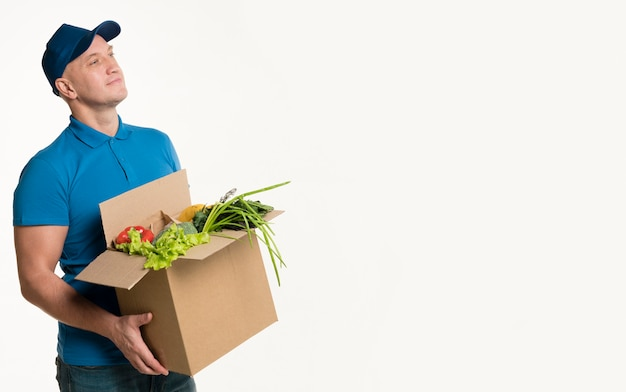 Delivery man holding grocery box with copy space