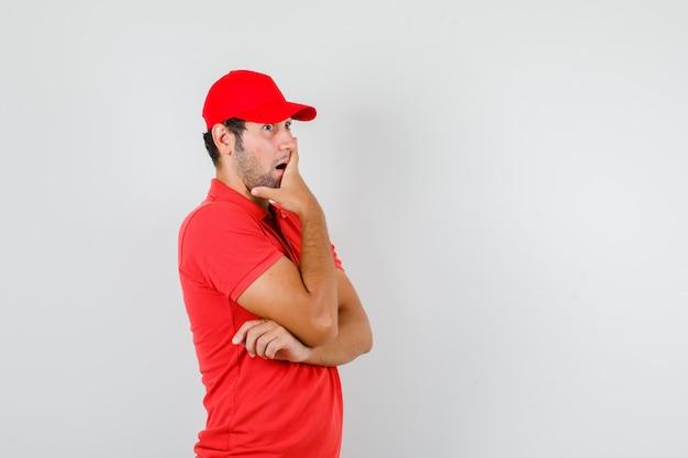 Uomo di consegna che tiene la mano sulla bocca in maglietta rossa