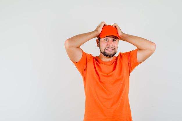 Fattorino che si tiene per mano sulla testa in maglietta arancione, berretto e sembra impotente. vista frontale.