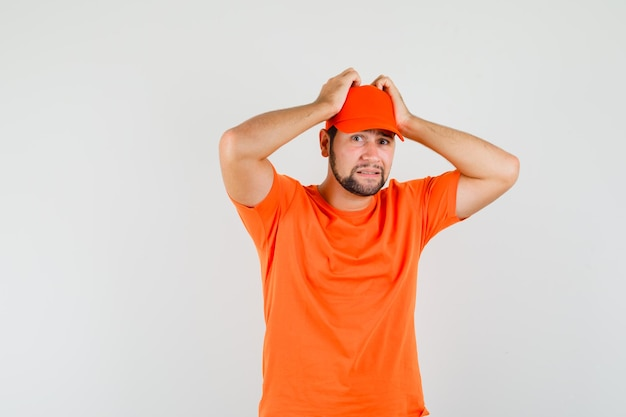 Fattorino che si tiene per mano sulla testa in maglietta arancione, berretto e guardando perplesso, vista frontale.