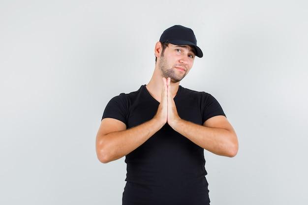 Доставщик, взявшись за руки в молитвенном жесте в черной футболке
