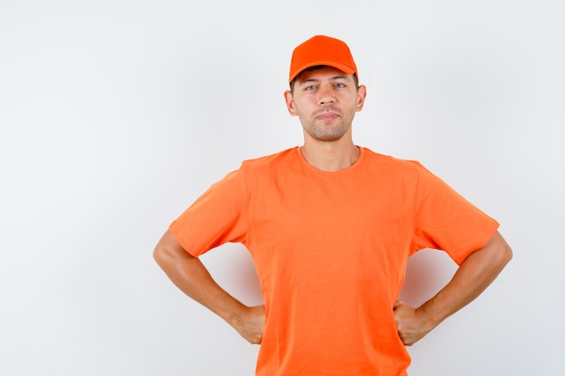 Delivery man holding hands on waist and smiling in orange t-shirt and cap front view.