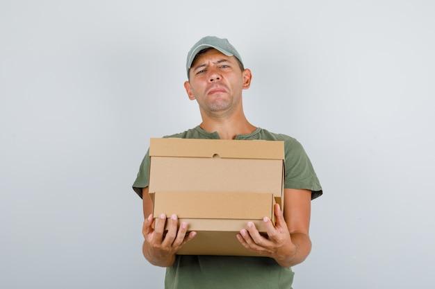 アーミーグリーンのtシャツ、キャップのフロントビューで重い段ボール箱を抱えて配達人。