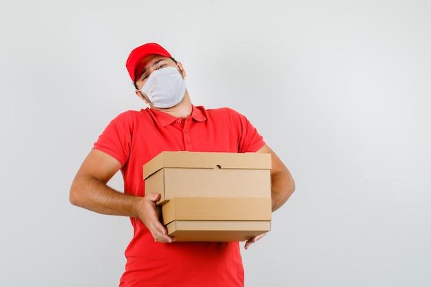 Доставщик, держащий тяжелые картонные коробки в красной футболке