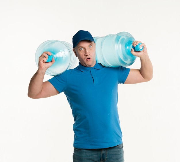 Delivery man holding heavy water bottles on shoulders