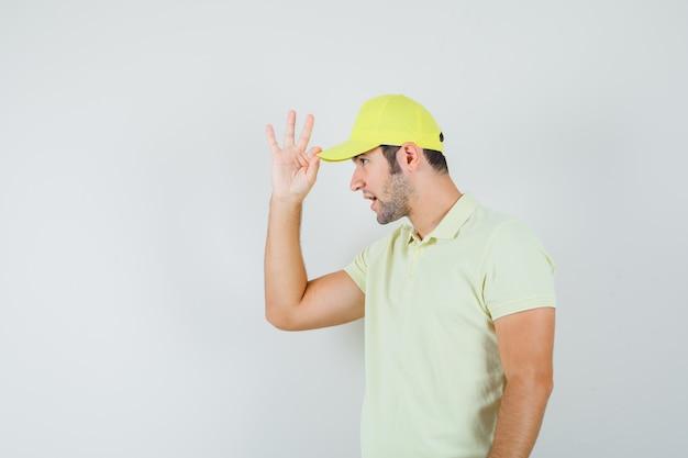 Uomo di consegna che tiene il suo cappello in uniforme gialla e che sembra bello. vista frontale.