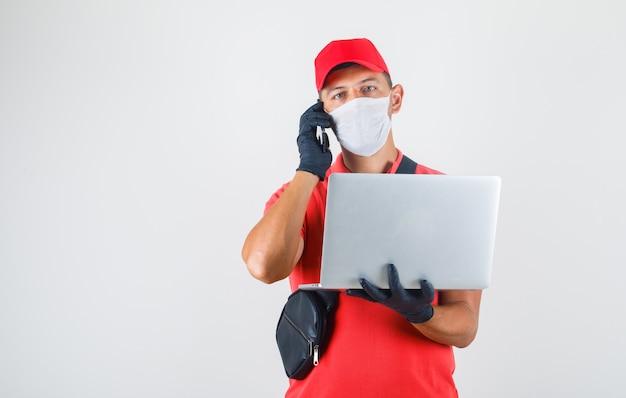 Доставщик держит ноутбук и разговаривает по мобильному телефону в красной форме