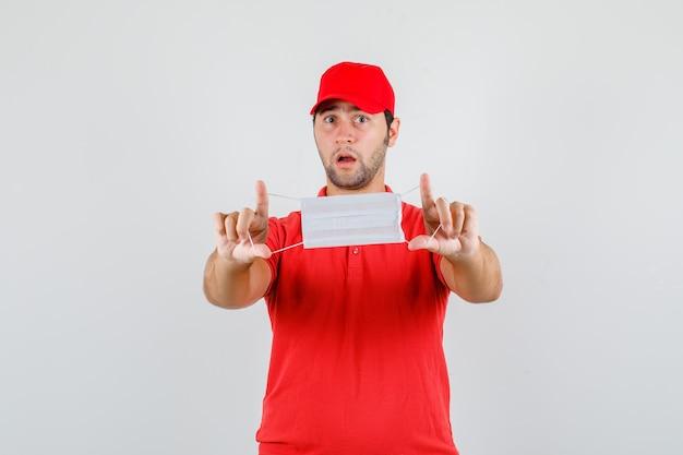 Uomo di consegna che tiene mascherina medica in maglietta rossa