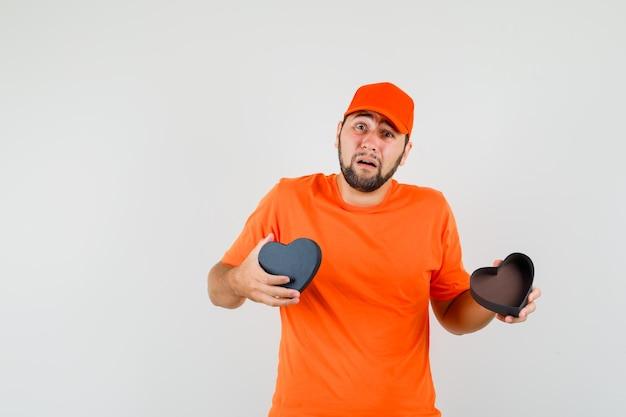 Fattorino che tiene in mano una confezione regalo aperta in maglietta arancione, berretto e guardando giù, vista frontale.