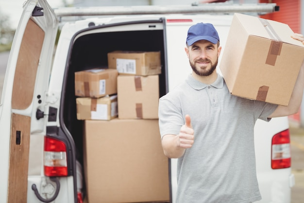 Delivery man holding package in front of his van