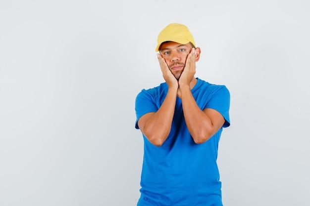 Uomo di consegna che tiene le palme sulle guance in maglietta blu