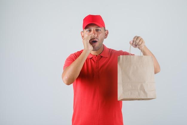 紙袋を押しながら赤い制服正面で身振りで示す配達人。