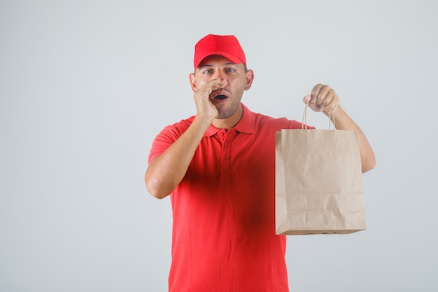 Delivery man holding paper bag and gesturing in red uniform front view.