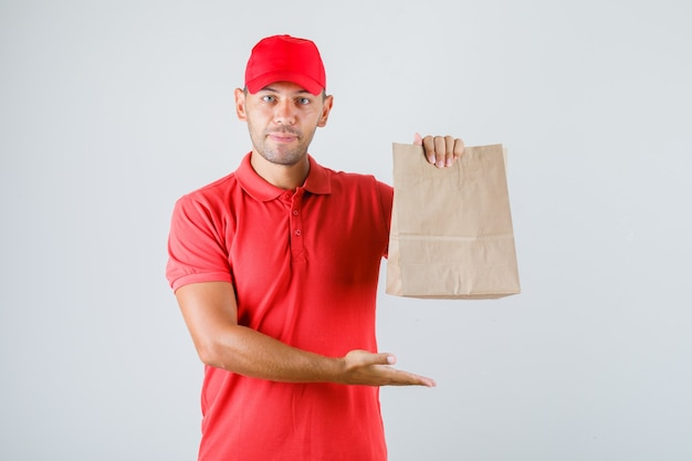 赤い制服を着た紙袋を保持している配達人