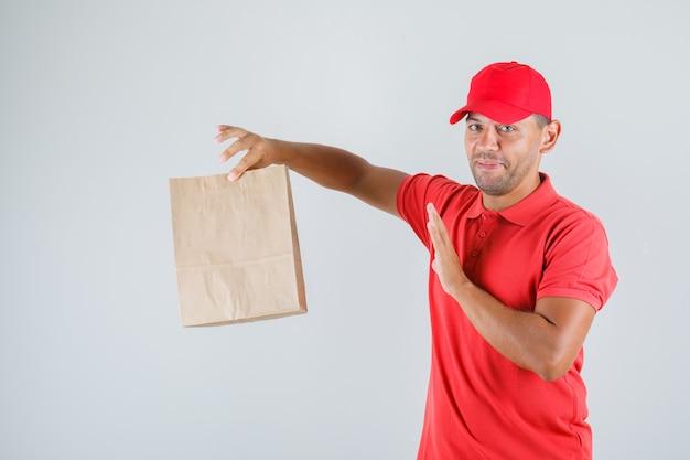 Uomo di consegna che tiene il sacchetto di carta in uniforme rossa e che sembra protettivo