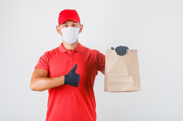 Delivery man holding paper bag and showing thumb up in red uniform
