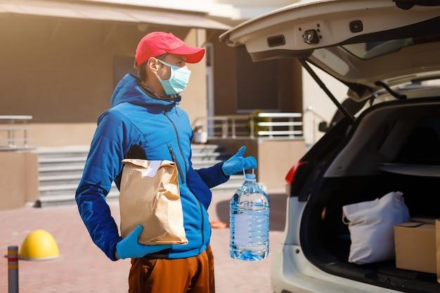 Доставщик еды держит бумажный пакет с едой возле машины, курьер в защитной маске