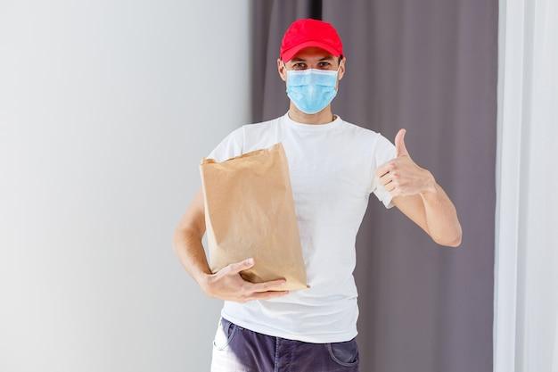 Доставщик еды, держащий бумажный пакет с едой на белом фоне, курьер в защитной маске
