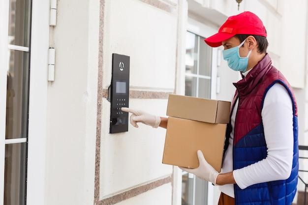 Доставщик еды, держащий бумажный пакет с едой на белом фоне у входа в дом, курьер в защитной маске